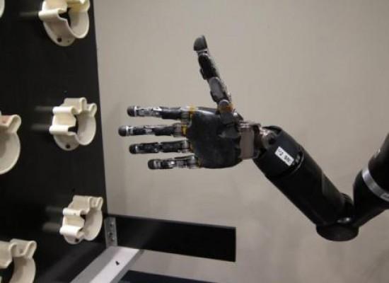 Mujer con parálisis logra levantar objetos gracias a su brazo robotico controlado por la mente.
