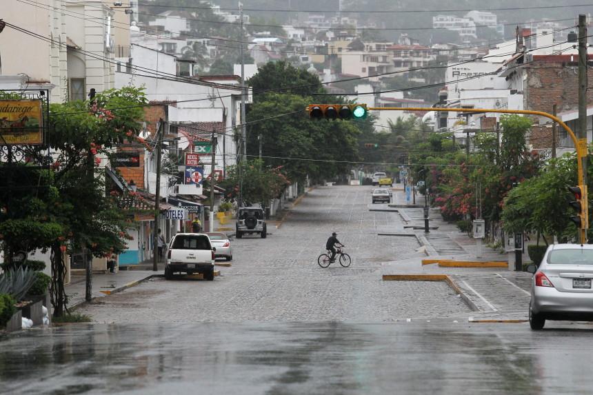 """MEX25. PUERTO VALLARTA (MÉXICO), 23/10/2015.- Un ciclista transita por una calle hoy, viernes 23 de octubre de 2015, en la ciudad de Puerto Vallarta en el estado de Jalisco (México). El peligroso huracán Patricia avanza con rapidez sobre aguas del Pacífico hacia la costa occidental de México y registra rachas de viento de 400 kilómetros por hora, informó hoy el Servicio Meteorológico Nacional (SMN). En su último boletín, detalló que a las 13.00 hora local (18.00 GMT) el meteoro, de categoría 5 en la escala Saffir-Simpson, es """"extremadamente peligroso"""" e indicó que se prevé que su ojo se acerque esta tarde a las costas de Jalisco, en el occidente de México. Patricia, que se encuentra a unos 135 kilómetros al suroeste de Manzanillo (Colima), provocará """"lluvias intensas a puntuales torrenciales"""", además de """"violentas rachas de viento y oleaje elevado en los estados del Pacífico Central"""", que ya empezaron a presentar en las costas de Michoacán, Colima y Jalisco. El huracán, con un diámetro de ojo de 9 kilómetros, se desplaza hacia el norte a 19 kilómetros por hora y desarrolla vientos sostenidos de 325 kilómetros por hora y rachas de hasta 400. EFE/Ulises Ruiz Basurto"""